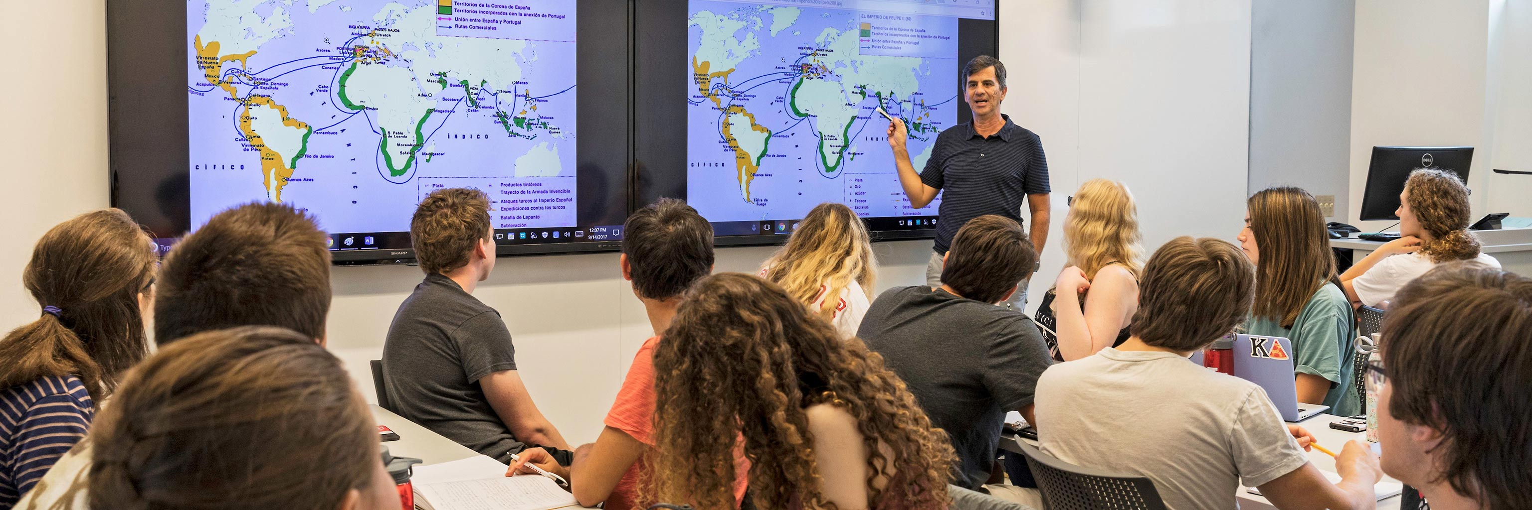 Instructor lectures in front of a world map to a class of students