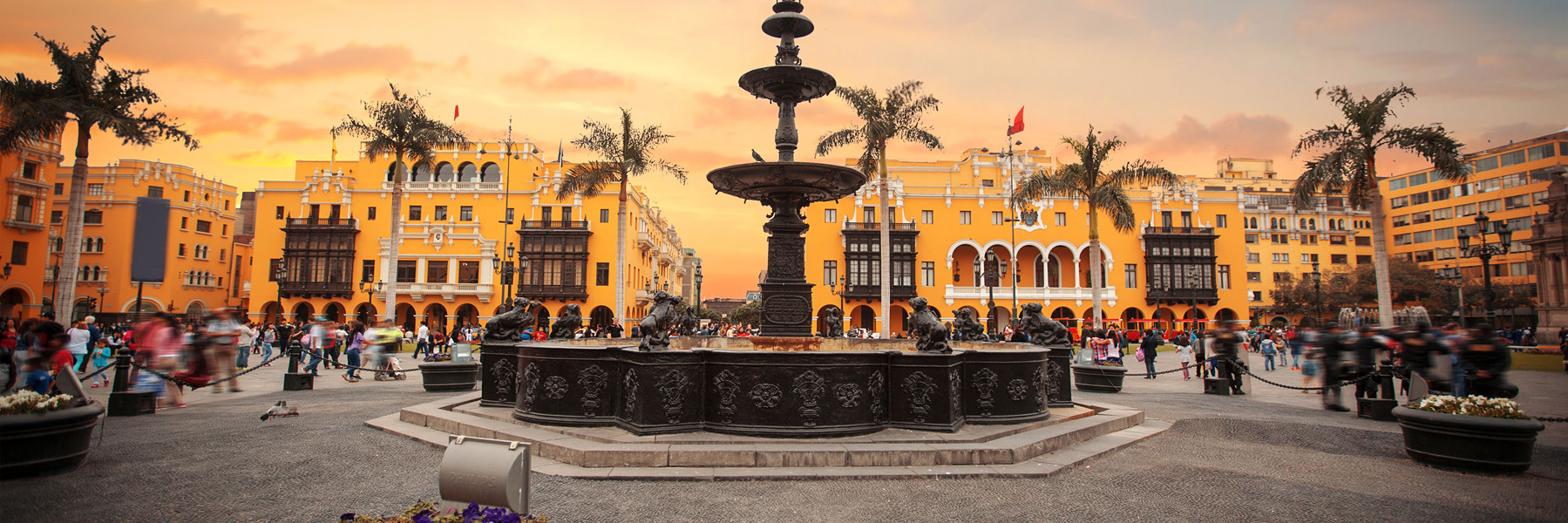 A fountain and bright yellow buildings in Lima, Peru