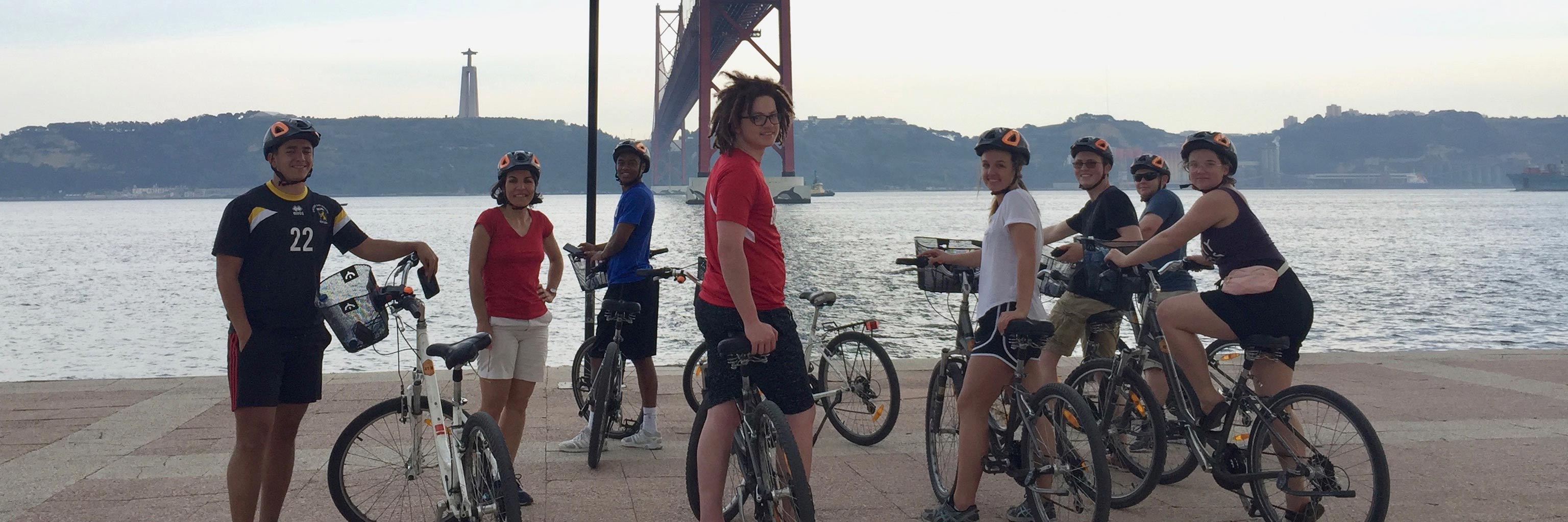 Students pose with their bikes on a waterfront