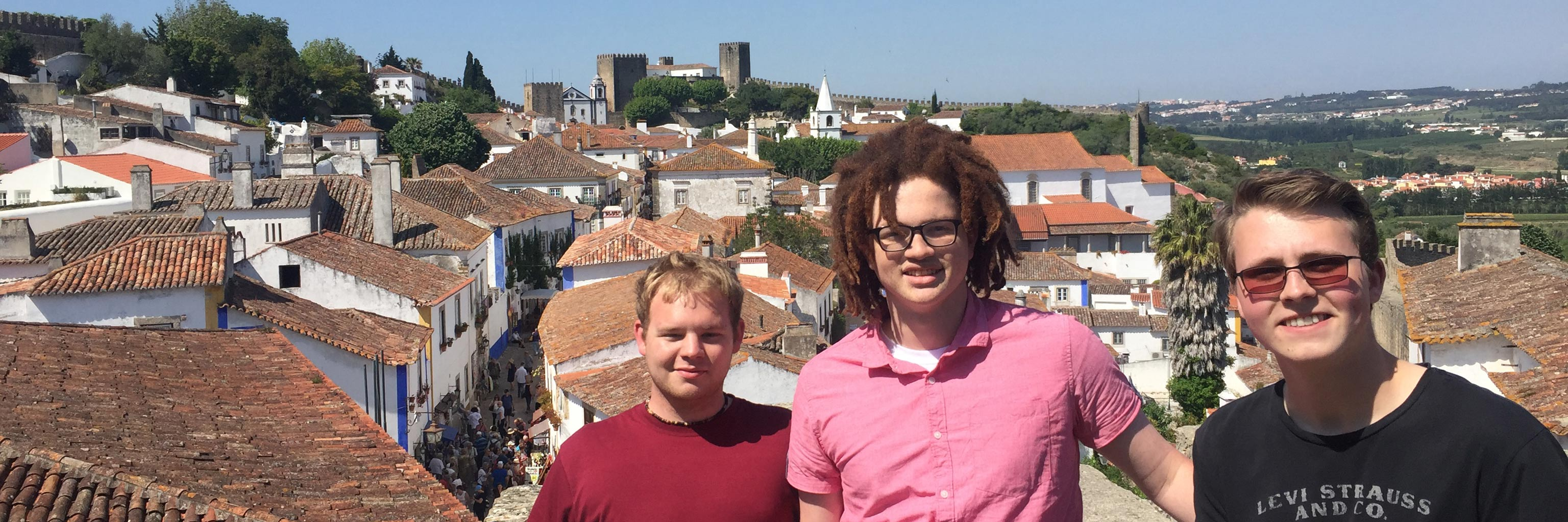Three students posing in front of rooftops in their study abroad destination